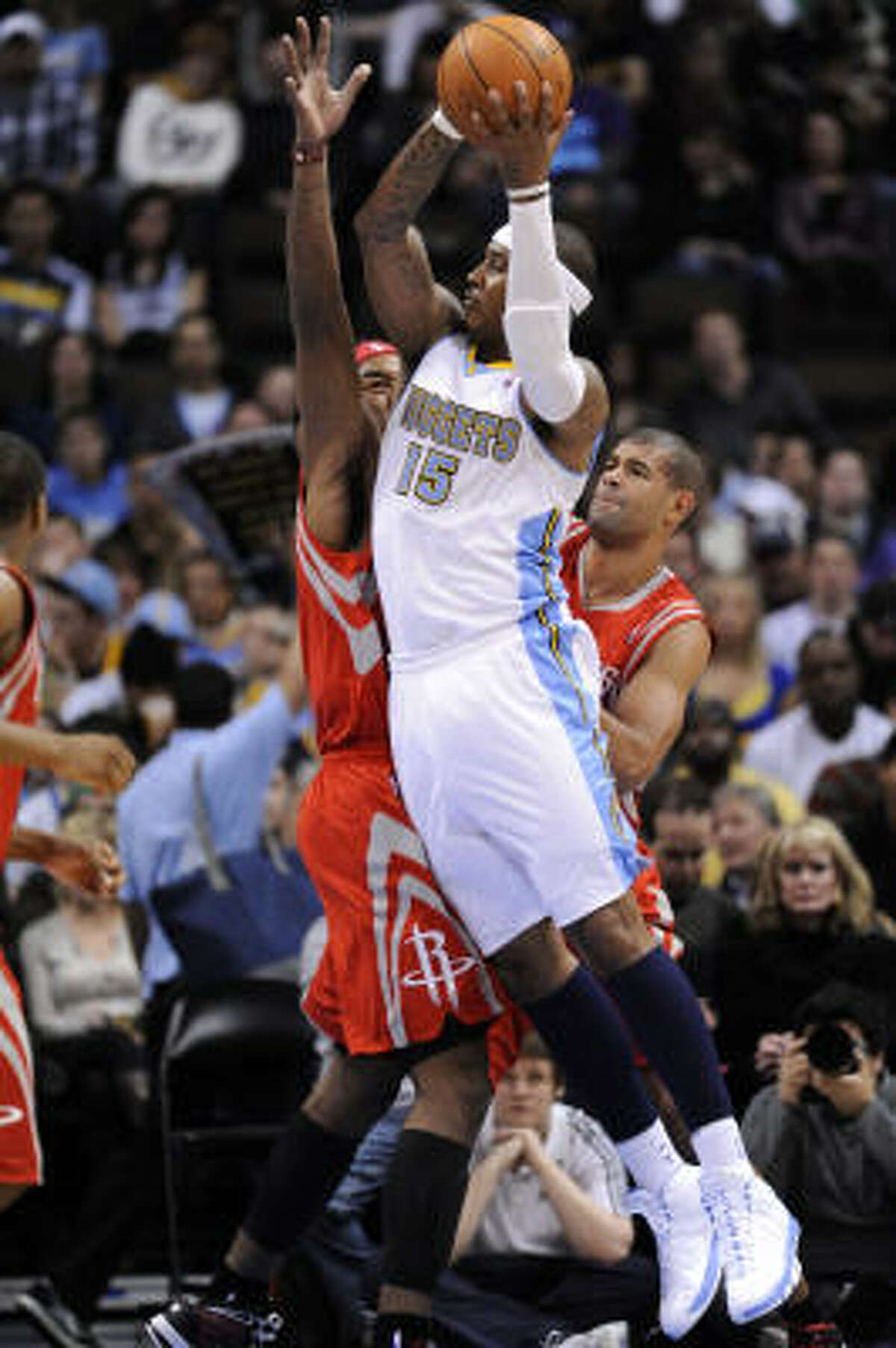 Nuggets forward Carmelo Anthony (15) goes up for a shot against Rockets forward Jordan Hill, left, and Shane Battier, right.