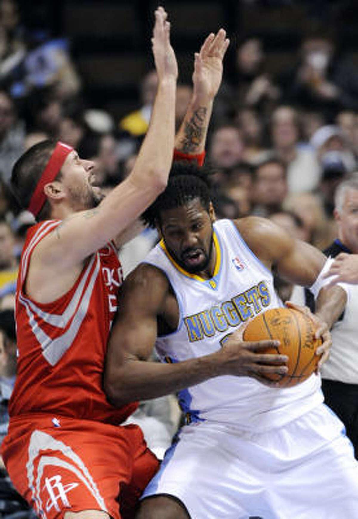 Nuggets center Nene (31) bumps Rockets center Brad Miller (52).