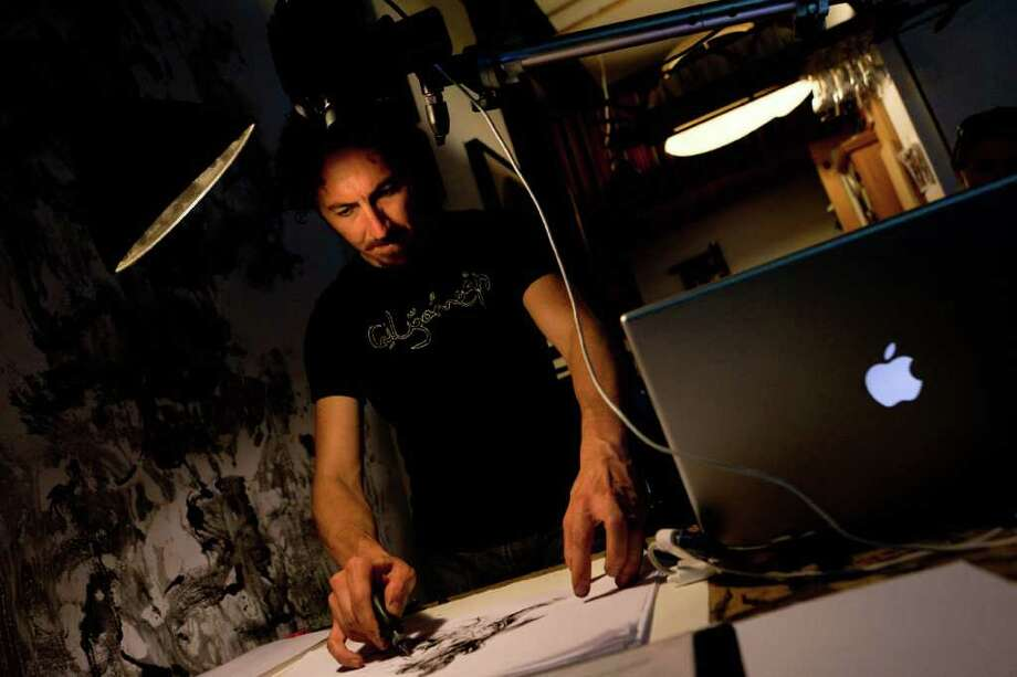 In this July 20, 2011 photo, renowned visual artist Kevork Mourad practices his drawing technique before a performance in his Bushwick studio in the Brooklyn borough of New York. Bushwick's sordid history as a gang territory is becoming overshadowed by the influx of artists flocking to the area in search of affordability and space. (AP Photo/John Minchillo) Photo: John Minchillo