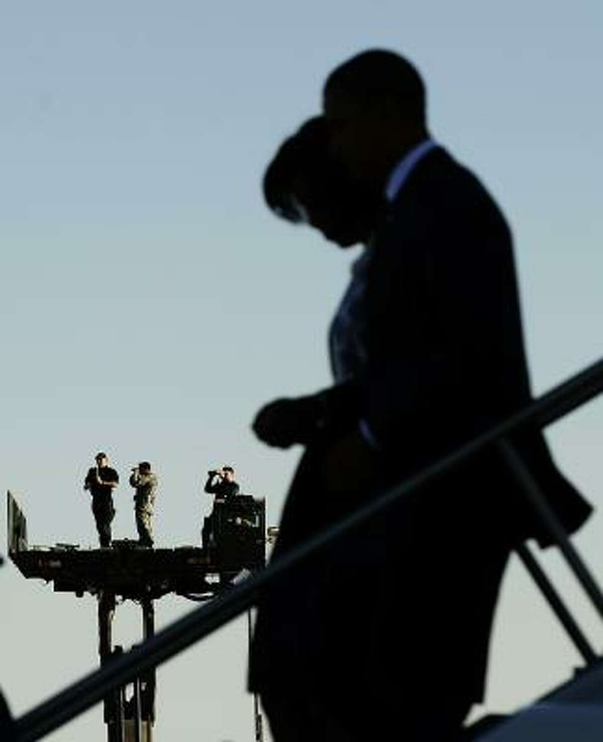 Security personnel keep vigil as US President Barack Obama and First Lady Michelle Obama disembark from Air Force One as they arrive at Davis-Monthan Air Force Base in Tucson, Arizona.