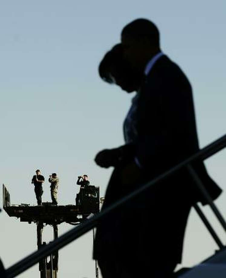 Security personnel keep vigil as US President Barack Obama and First Lady Michelle Obama disembark from Air Force One as they arrive at Davis-Monthan Air Force Base in Tucson, Arizona. Photo: JEWEL SAMAD, AFP/Getty Images