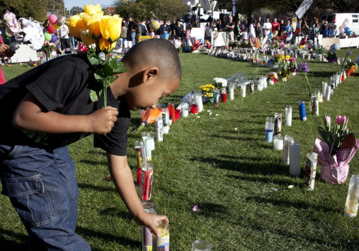 Devonte Green, 5, of Tucson, Ariz., places his candle at the makeshift memorial to Rep. Gabrielle Giffords and other victims of the Saturday's shootings in front of University Medical Center in Tucson.