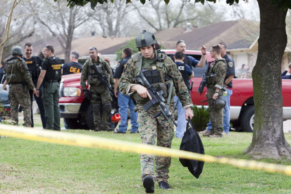 A Houston Police Department SWAT member leaves a raid where an officer was wounded Thursday. Two suspects were arrested, including one who was shot in a north Houston house. The officer is expected to survive; the suspect was listed as stable.