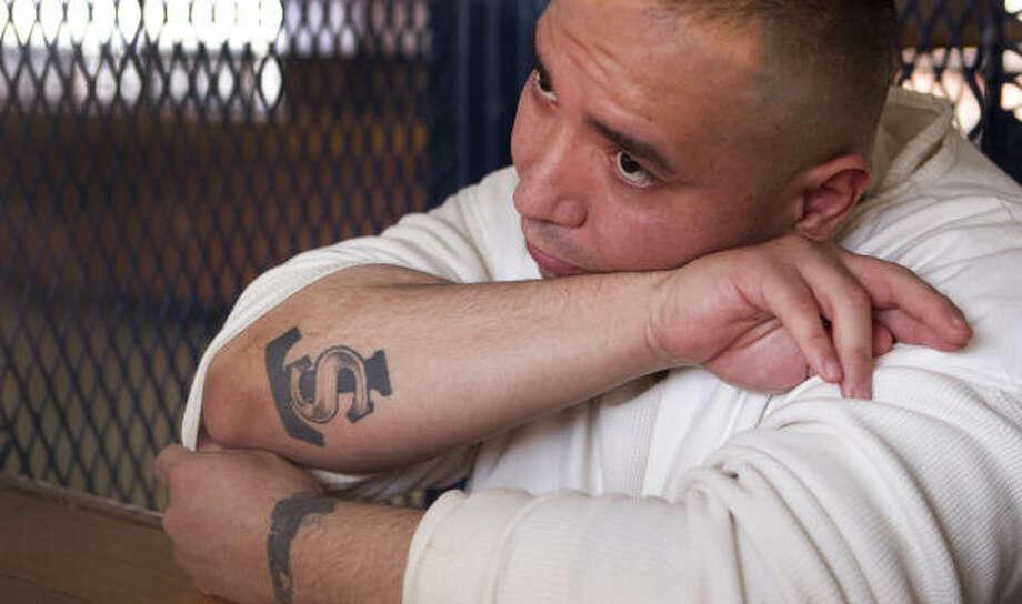 Mike Mendoza, Jr. muestra su tatuaje de la pandilla Texas Syndicate en el área de visita de una prisión de Midway. Photo: Brett Coomer, Houston Chronicle