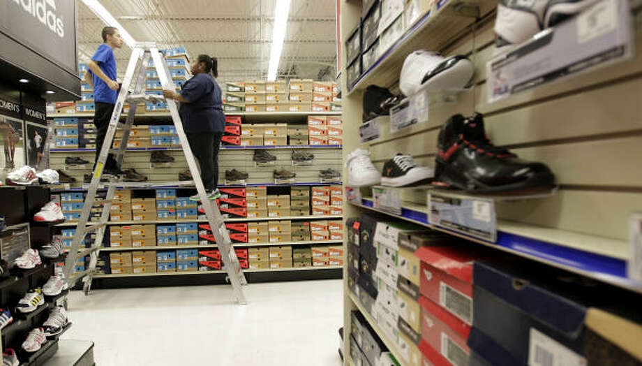 Eric Granados and Sade Sands move shoeboxes on a top shelf last month as they and other workers stocked the new 90,000-square-foot Academy Sports + Outdoors in Humble. Photo: Karen Warren :, Chronicle