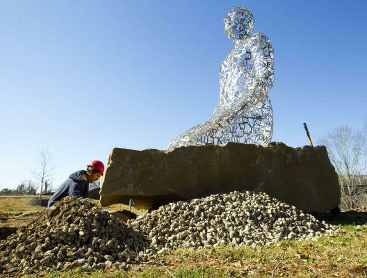 Mario Chavez fills in rock under the base of one of the Tolerance sculptures in an effort to finish the project near Allen Parkway and Montrose on Friday. The sculptures, by Jaume Plensa, are scheduled to be dedicated this week.