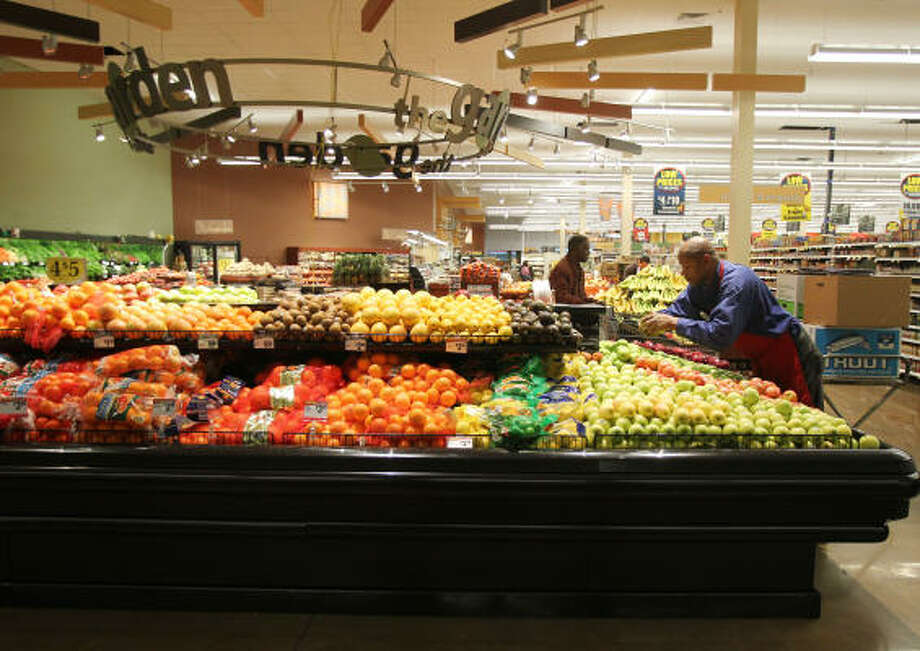 Kroger employee Ricky Roberson stocks a produce case at the Kirby and South Main store, which is well into its remodeling. Photo: James Nielsen:, Chronicle