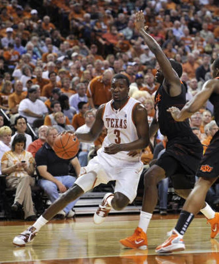 Texas forward Jordan Hamilton drives the lane against Oklahoma State forward Jean-Paul Olukemi. Photo: Michael Thomas, AP
