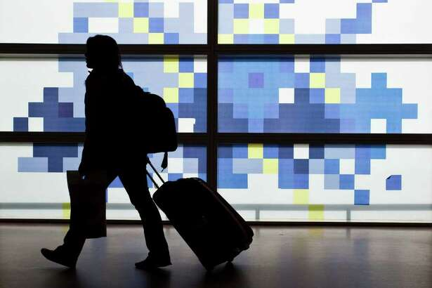 A passenger wheels her luggage past an illuminated wall at BAA Ltd.'s Glasgow airport in Glasgow, Scotland, on Friday, July 29, 2011. BAA Ltd. was last week ordered to sell Stansted, a base for discount carriers including Ryanair Holdings Plc, and an airport in either Edinburgh or Glasgow after the latest U.K. Competition Commission ruling in a four-year tussle. Photographer: Mike Wilkinson/Bloomberg