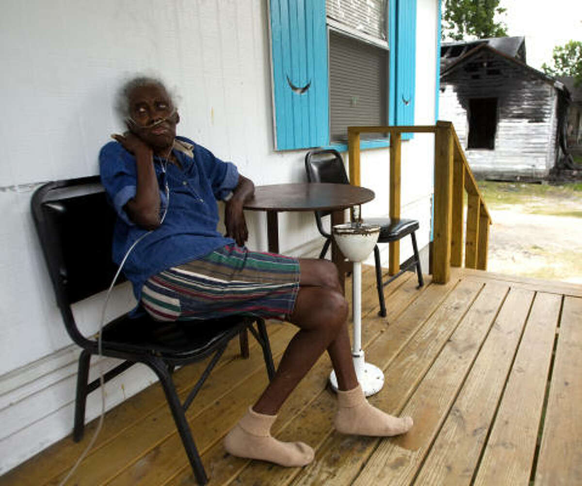 Earnestine Brown sits on her porch next to the rental home in Houston where her niece suffered fatal injuries when it burned down in August 2009. The family had complained about electrical problems; it later settled a suit with BMI Investment.