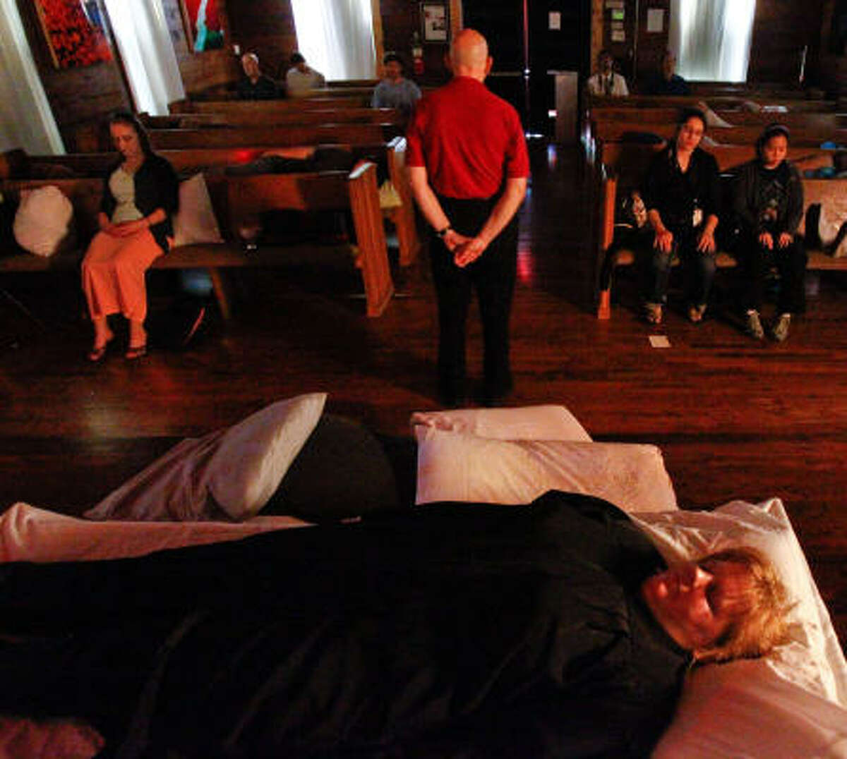 Performance artist Emily Sloan, front, relaxes on Sunday with other participants at 14 Pews in the Heights during the first Southern Naptist Convention, Stan Merrill of The Jung Center of Houston, standing, leads in meditation sequence.
