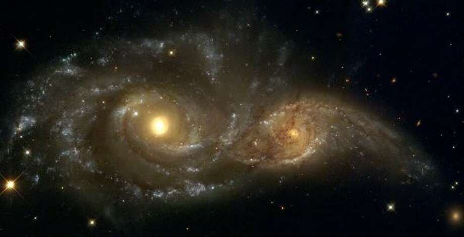 In the direction of Canis Major, spiral galaxies pass each other like majestic ships. Photo: NASA; ESA; HUBBLE HERITAGE TEAM