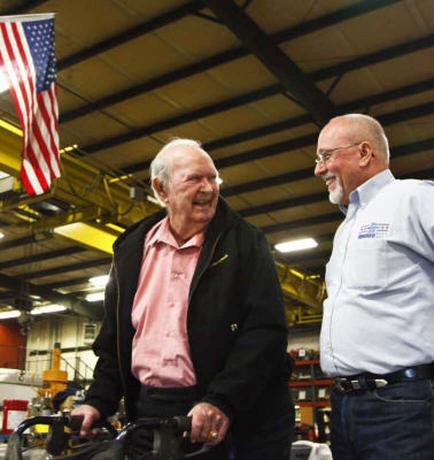 Larry Keast, right, owner of Venturetech, applauds 87-year-old Cecil Kirkland for continuing his working career at Navajo Fishing & Rental Tools during Geezerfest on Thursday. Keast has started America in Recovery, an organization that operates an Internet job site for seniors. Photo: Michael Paulsen, Chronicle