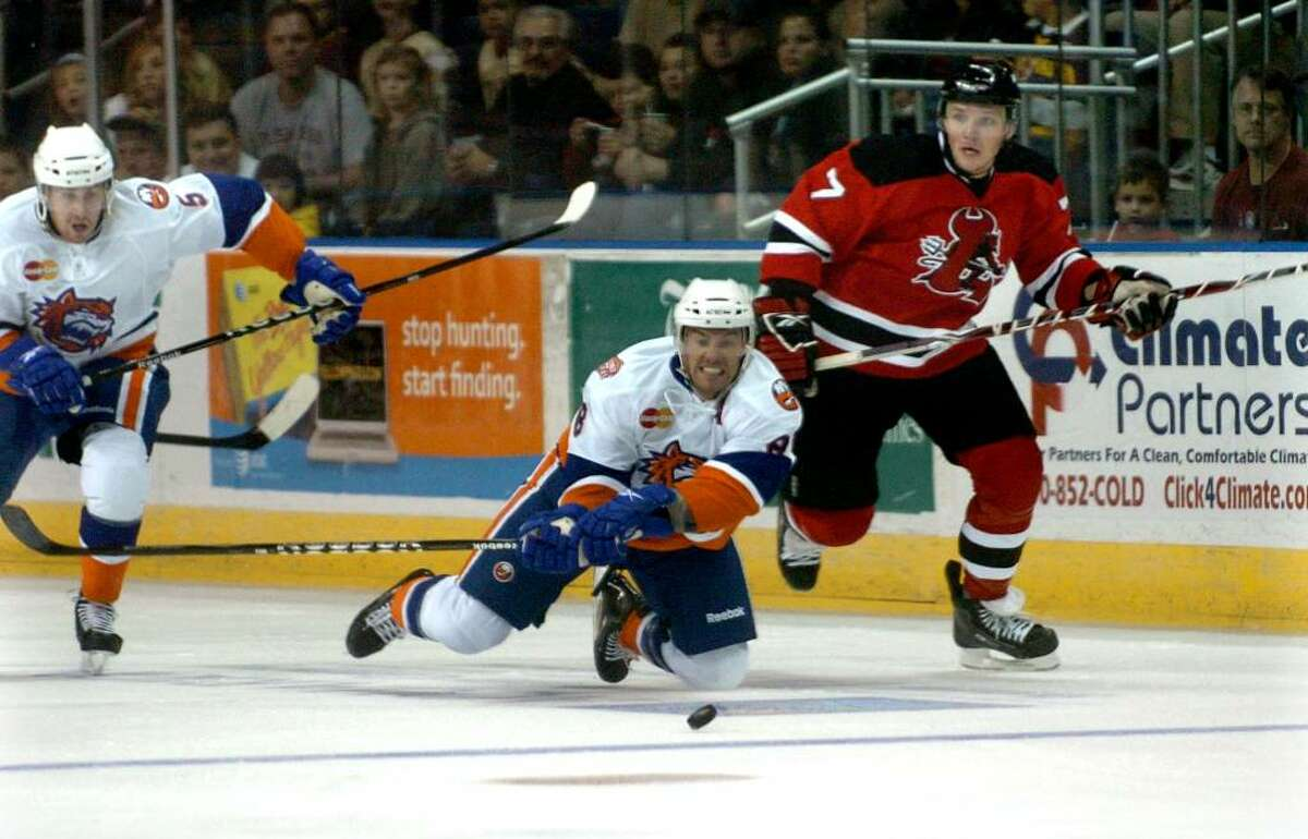 Sound Tigers #8 Greg Moore, center, plunges towards the puck, during season opening game action against the Lowell Devils in Bridgeport, Conn. on Saturday Oct. 03, 2009. At right is Lowell's #7 Tyler Eckford.