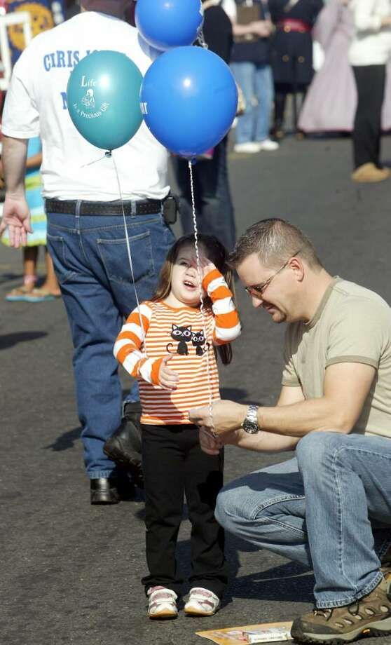Bill Sura ties a balloon around his, 3 year old, daughter Emily on Howe Avenue during Shelton Day, Sunday, Oct. 4, 2009. Photo: Phil Noel / Connecticut Post