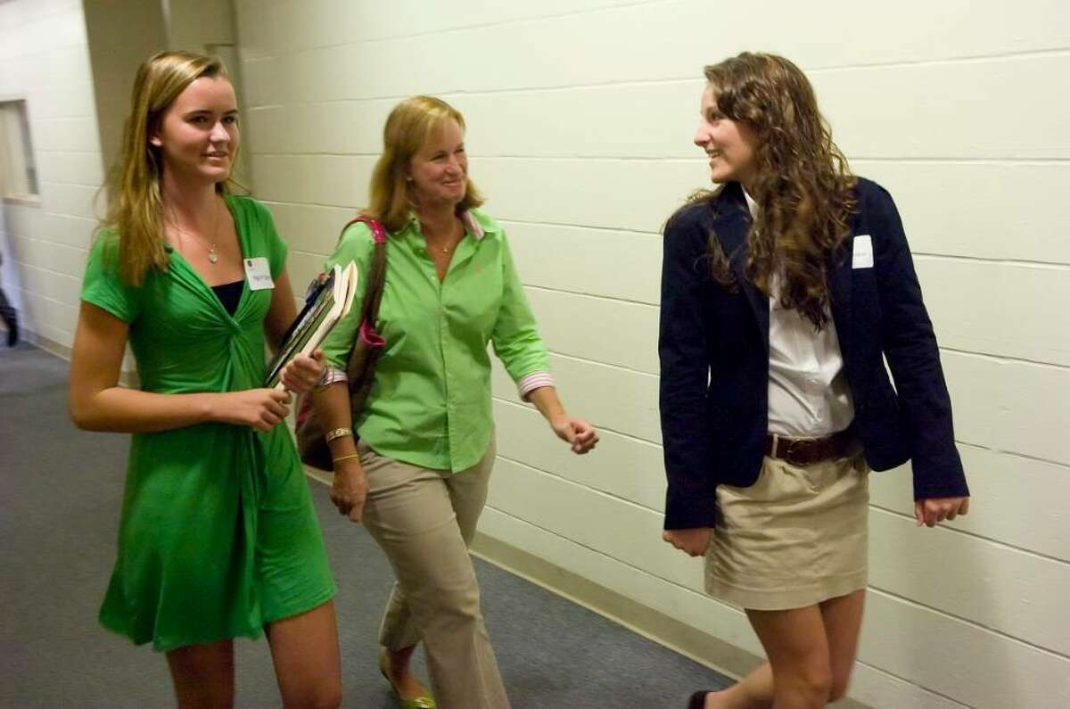 King school sophomore Kaleen (cq) Sullivan, 15, right, escorts Kylis GLover, 15, left, and her mom Diane Glover, center, to the gym during an open house at the King school in Stamford, Conn. on Sunday, Oct. 4, 2009.