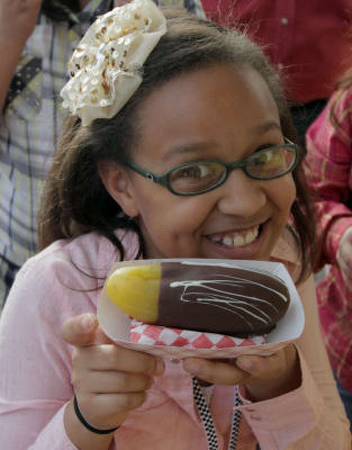 Ryan Llorens, 9, shows off her chocolate-covered pickle at the Houston Livestock Show and Rodeo.