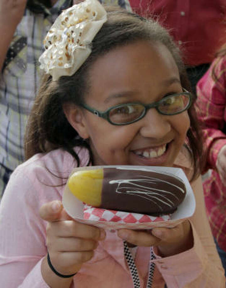 Ryan Llorens, 9, shows off her chocolate-covered pickle at the Houston Livestock Show and Rodeo. Photo: Tonya Torres, Chronicle