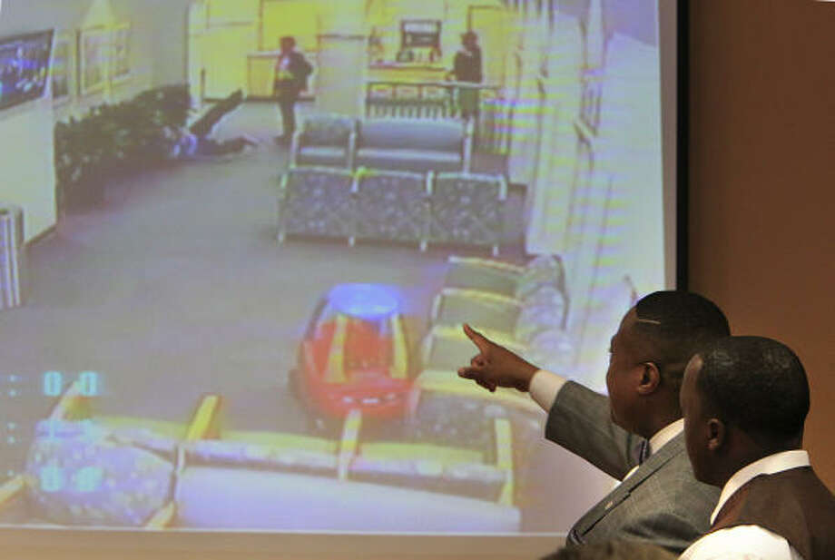 Quanell X, left, describes the alleged police brutality suffered by Henry Lee Madge, right, in a video shown at The Community of Faith Church. Photo: Mayra Beltran, Chronicle