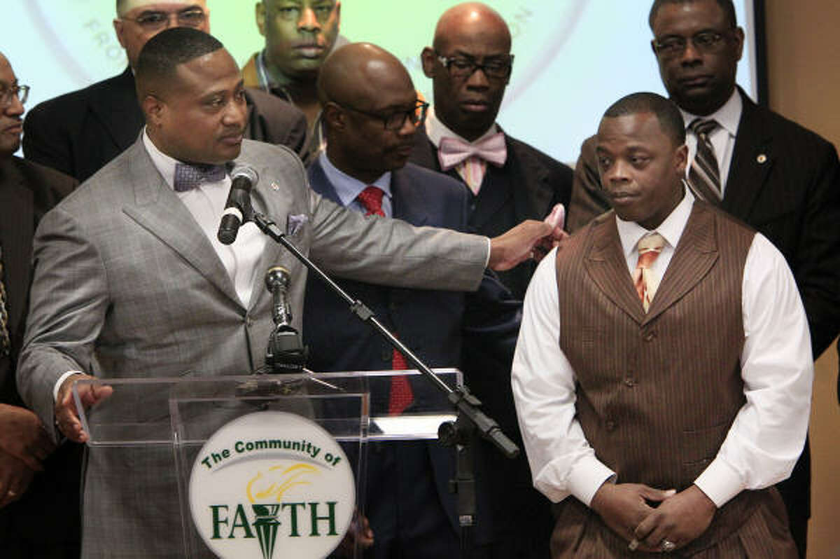 Quanell X, left, on Thursday introduces Henry Lee Madge, 27, who says he was attacked by a Houston police officer for no reason and that he lost his job because of the incident.