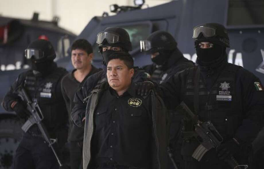 "Federal Police agents escort Flavio Mendez Santiago, center, alias ""El Amarillo,"" alleged member and co-founder of the Zetas drug cartel, during a presentation to the media in Mexico City, Tuesday. Photo: Alexandre Meneghini, Associated Press"