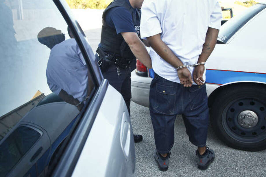 Houston police officers process a suspected drug dealer. Tips to the department's website, stophoustongangs.org, have helped score 30 felony and misdemeanor arrests in recent months. Photo: Michael Paulsen, Chronicle