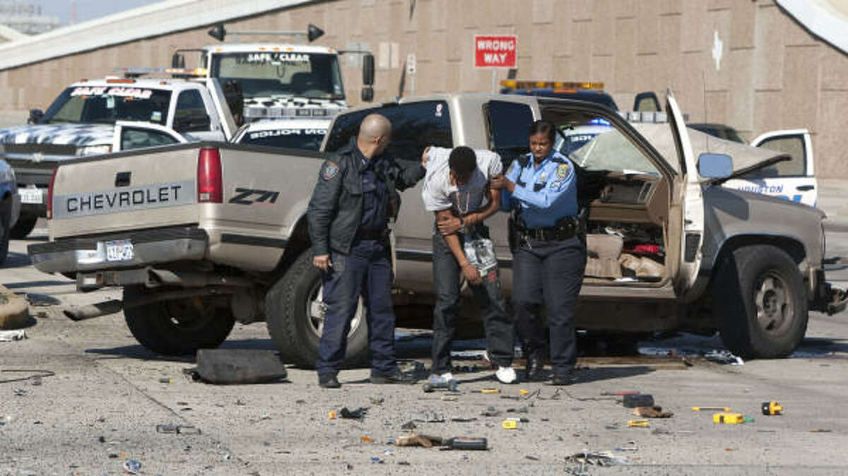A police officers help a stolen vehicle suspect to his feet following a chase that ended in a wreck Tuesday at the intersection of Quitman and the Eastex Freeway.