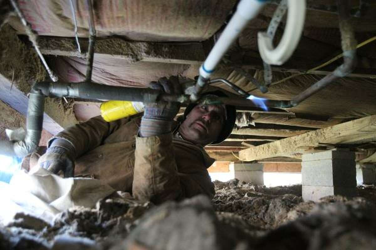 Wayne Bowman with Clayton Lee Plumbing thaws frozen pipes with a torch at a home in the 1600 block of Oxford on Wednesday.