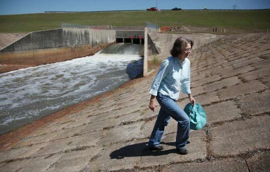 Evelyn Merz, of the Sierra Club, walks Friday along the south banks of the dam at Addicks reservoir. Merz and others with the Sierra Club are concerned that development around the dam will have a harmful environmental impact. Photo: Mayra Beltran, Chronicle