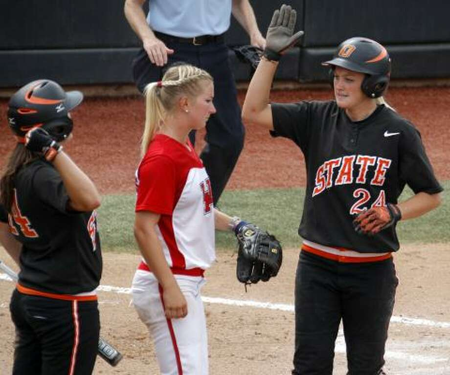 Oklahoma State's Julie Ward, right, and Tamara Brown celebrate beside UH's Donna Bourgeois during Game 3 on Saturday. Photo: Bryan Terry, Associated Press