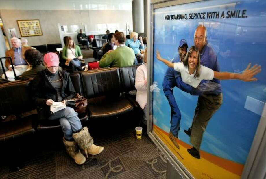 Passengers near a Southwest Airlines advertisement at Hobby Airport wait earlier this month to board one of the airline's flights to Panama City, Fla. Photo: Johnny Hanson :, Chronicle