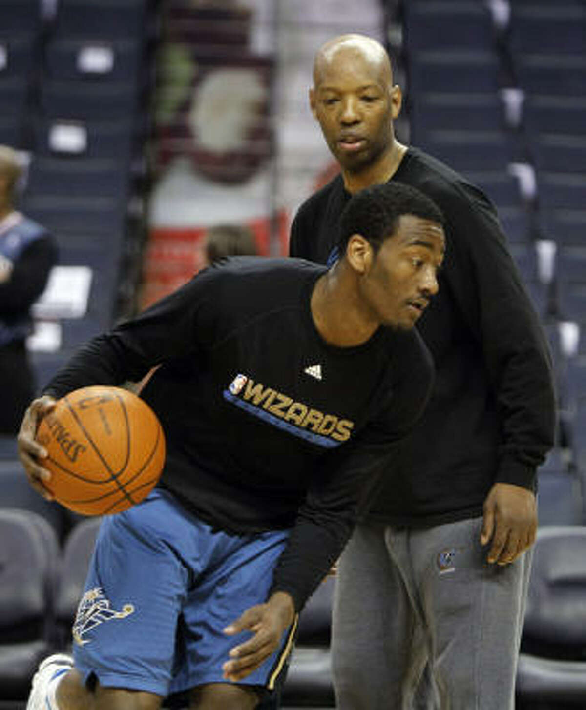 Former Rockets guard Sam Cassell, back, is currently an assistant coach with the Washington Wizards.