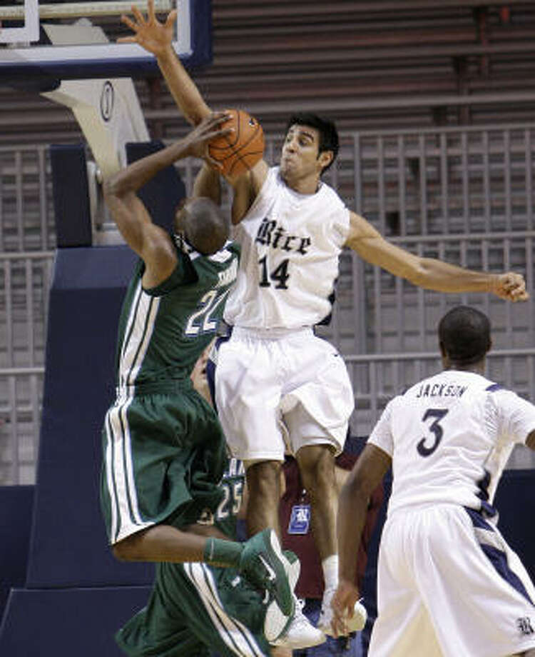 Rice's Arsalan Kazemi blocks a shot by Tulane's Kevin Thomas. Photo: Bob Levey, For The Chronicle