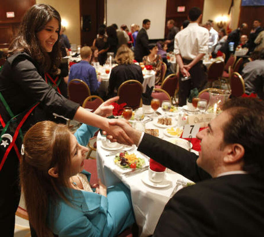 University of Houston freshman Hadeel Bunkheila, 19, greets guests at a dinner to raise awareness for the Libyan people at the Hilton Houston Westchase. The April 23 event raised more than $178,000 for humanitarian aid in Libya. Photo: Cody Duty, Chronicle