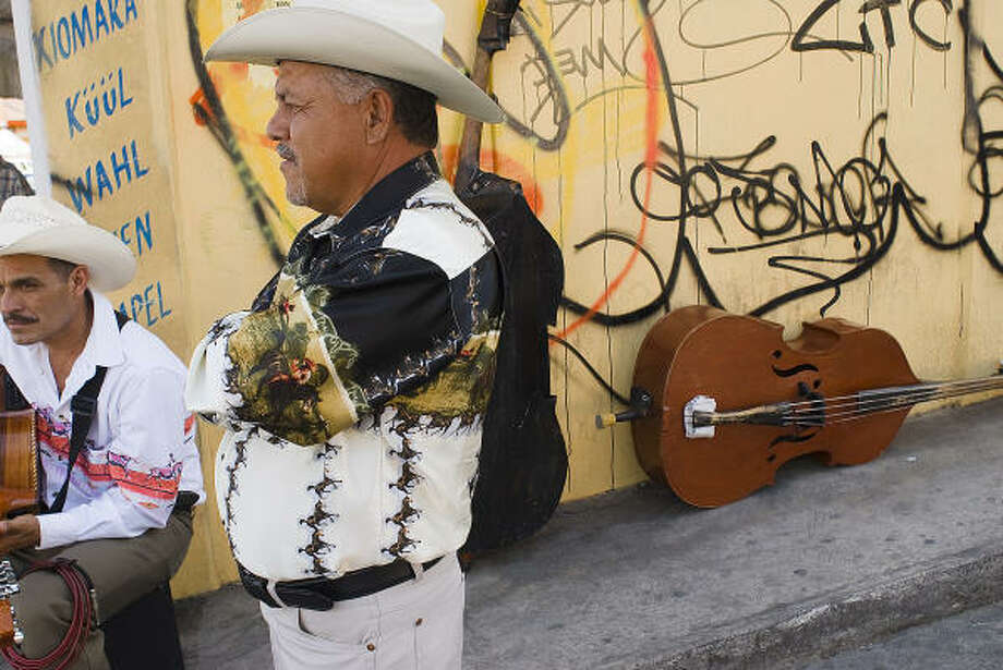 Traditional Norteño musicians wait for work on a street corner in front of a wall tagged with gang graffiti in Tejalpa, Mexico. The town, founded in the 16th century, and recently swallowed up by the urban sprawl of Cuernavaca, has experienced a growing crime problem. Photo: Keith Dannemiller, For The Chronicle