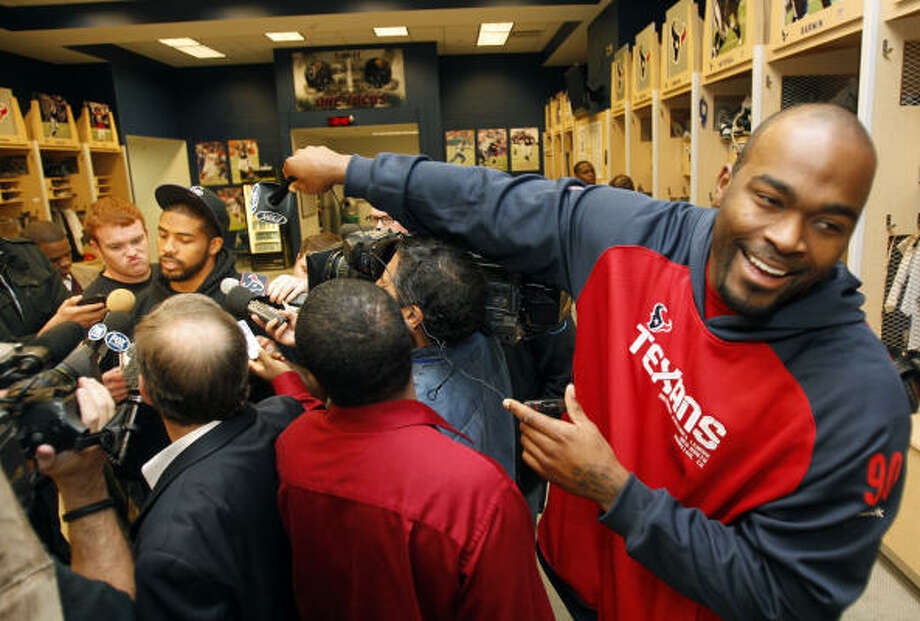 Texans defensive end Mario Williams, right, playfully adds a microphone to the crowd of media around newly crowned NFL rushing champion Arian Foster on Monday. Photo: Melissa Phillip, Chronicle