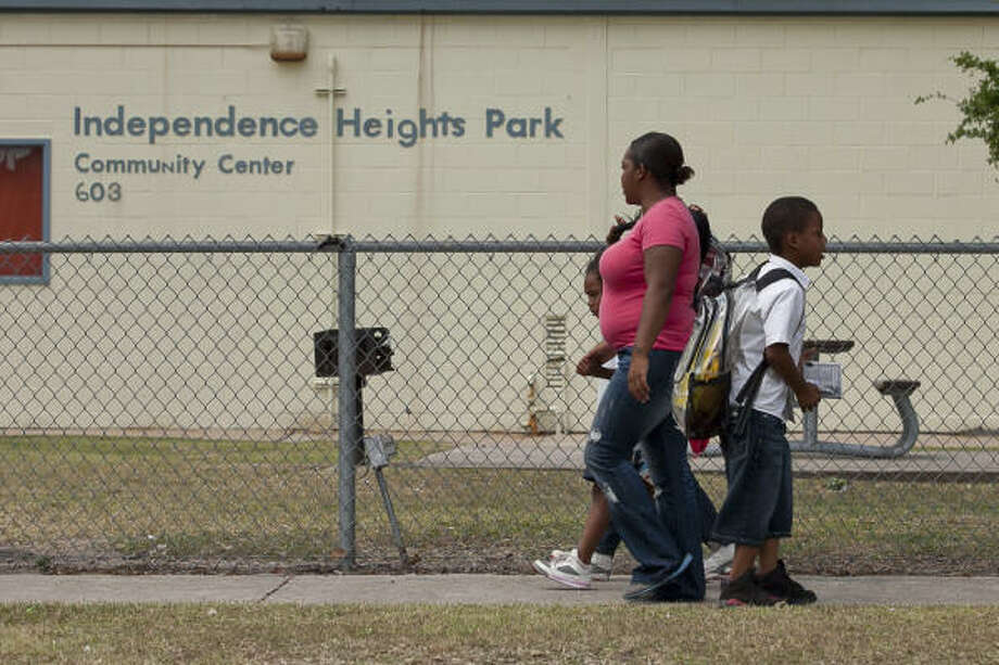 A mom walks her children home from Burrus Elementary on Friday. Independence Heights' community center and swimming pool are victims of the city budget. Photo: Nathan Lindstrom, Chronicle