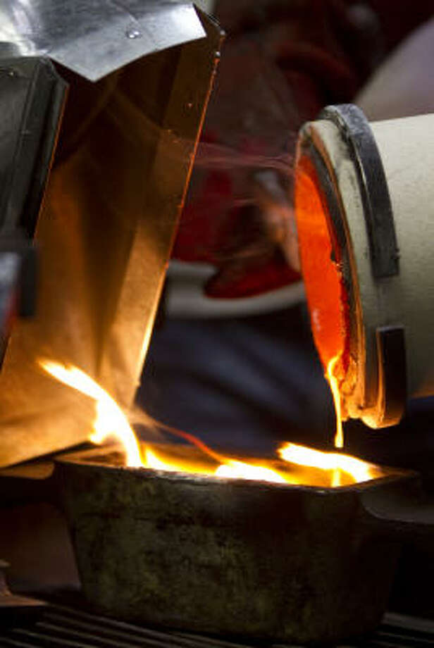 A local gold refiner is careful to get every drop out into the mold because each one can be worth a small fortune. After businesses purchase gold jewelry from sellers, some of it is sold, but much is melted down and ends up in gold bars like the one being created here. Photo: Nick De La Torre :, Houston Chronicle