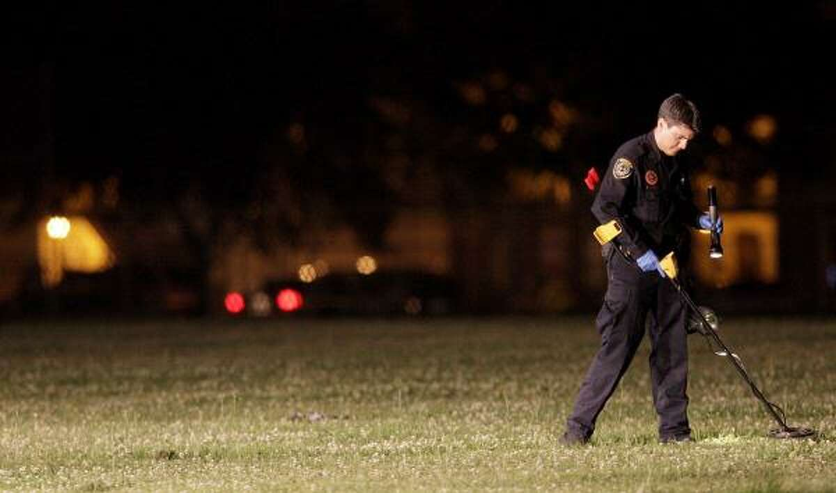 An officer uses a medal detector, a flashlight and lights from a Houston Department Fire truck to investigate the scene of the shooting.
