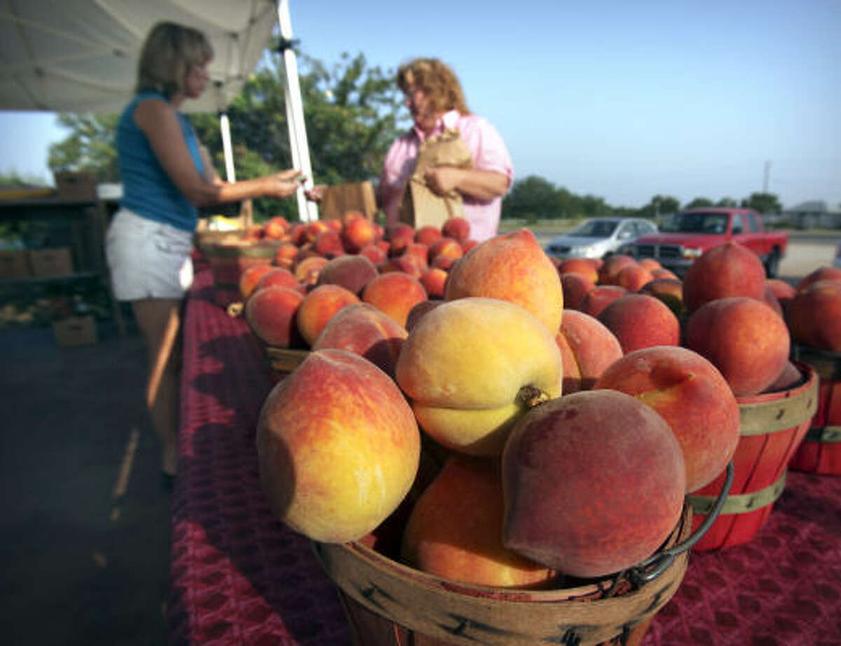 Lori Studebaker, left, sells a basket of the new peach crop to Dawni Nelson from New Mexico at the Studebaker Farm stand outside Fredericksburg.