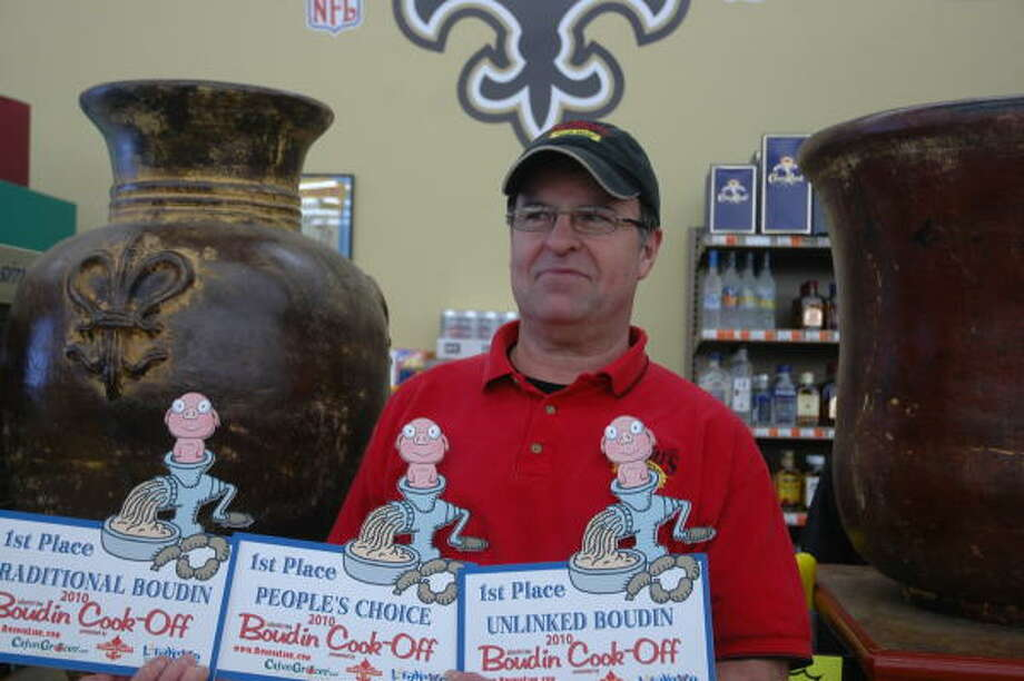 David Choate, boudin master for NuNu's groceries in Youngsville and Milton, La., south of Lafayette, displays the three first-place trophies NuNu's received in the fourth annual Boudin Cook-Off last October. Photo: JOAN SHATTUCK