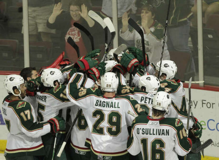 Aeros players mob winger Carson McMillan after he scored in overtime. Photo: Cody Duty, Chronicle
