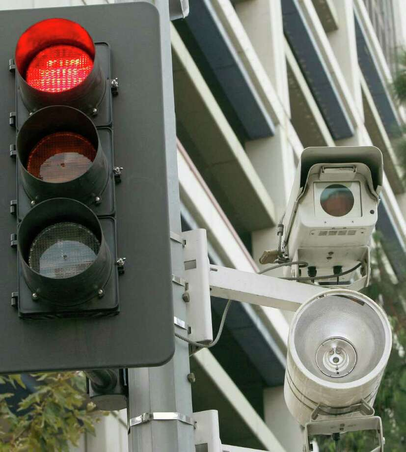 At least three dozen Texas cities use red-light cameras. This one, in Los Angeles, was turned off Sunday, along with the other 31 cameras in the program, because of difficulty collecting fines. Houston has collected $44 million since 2007. Photo: Associated Press File Photo