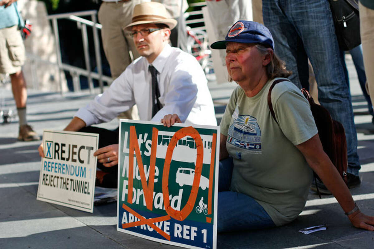 Demonstrators listen to anti-tunnel speeches at the City Hall Plaza in Seattle on Monday.