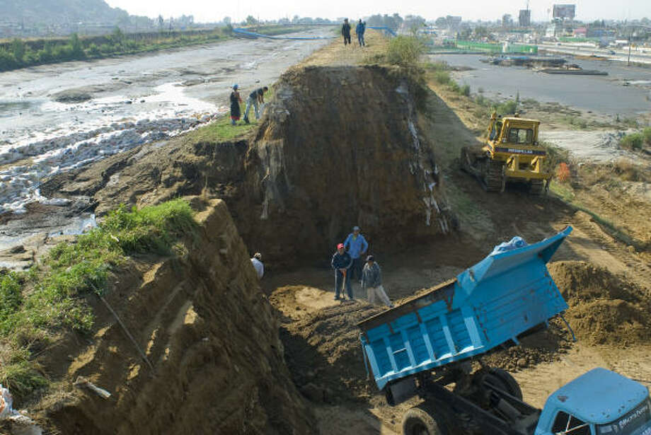 A dump truck empties its load to repair an earthen levee that collapsed Sunday on the outskirts of Mexico City. The Rio Compania canal was built to carry sewage and rainwater but can't handle the capital's rapid expansion. Photo: Keith Dannemiller, Chronicle