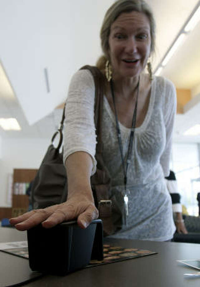 Ronda Wendler, editor of Texas Medical Center News, places her palm on a biometric scanner at Martin Luther King Health Center to map her veins with infrared technology. Photo: Cody Duty, Houston Chronicle