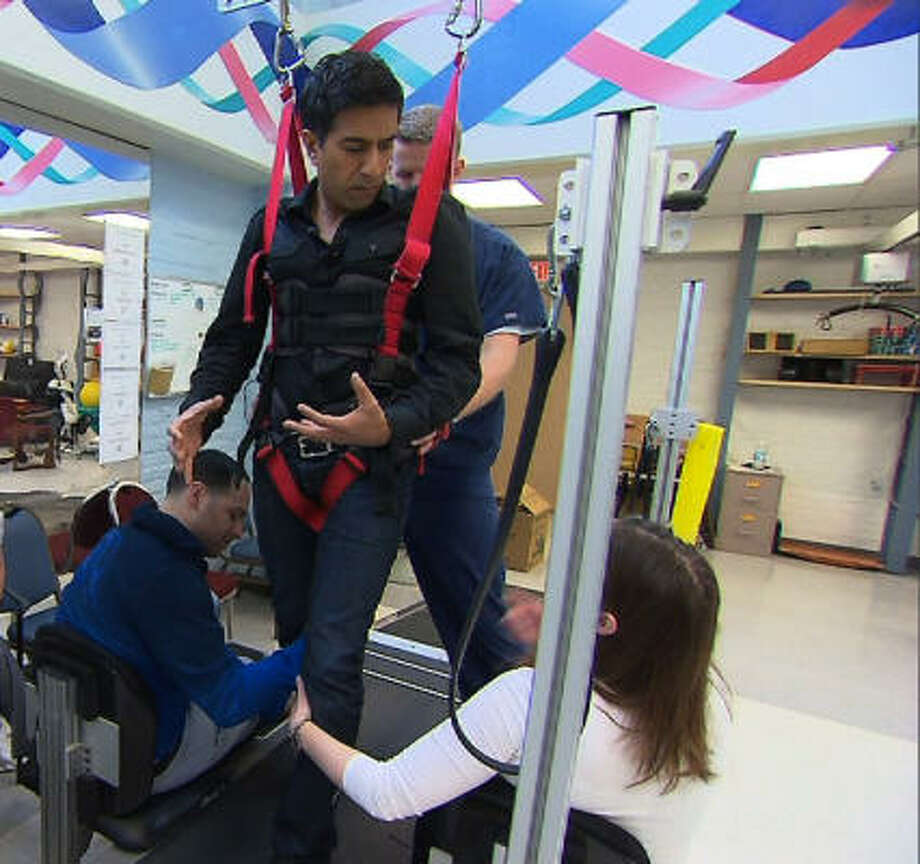 CNN medical correspondent Dr. Sanjay Gupta is strapped to equipment at The Institute for Rehabilitation and Research Memorial Hermann. It's part of an eight-hour simulation of the typical day of rehab for U.S. Rep. Gabrielle Giffords as part of a CNN documentary. Photo: CNN