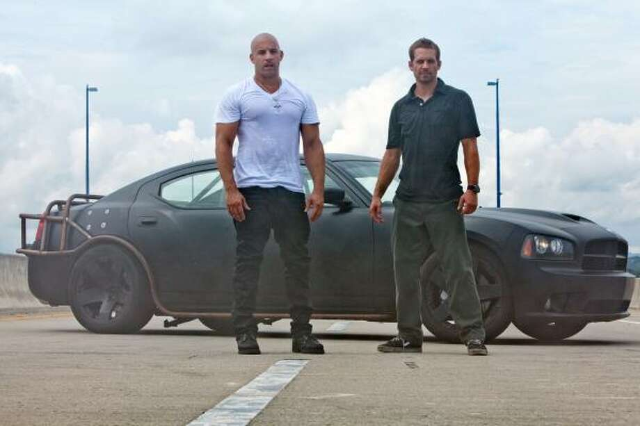 "Vin Diesel, left, and Paul Walker are shown in a scene from ""Fast Five."" Photo: Universal Pictures"