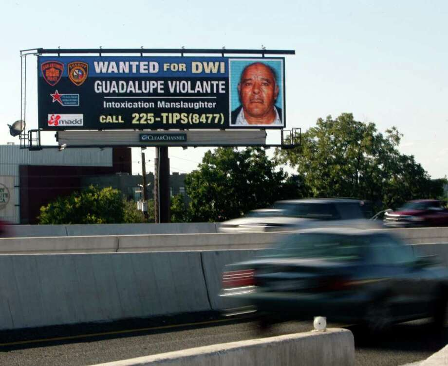 Motorists pass an electronic billboard at the I-37 and I-35 interchange that shows a suspect with an active warrant for a DWI-related offense. Subjects are encouraged to turn themselves in. Photo: Omar Perez/operez@express-news.net / SAN ANTONIO EXPRESS-NEWS