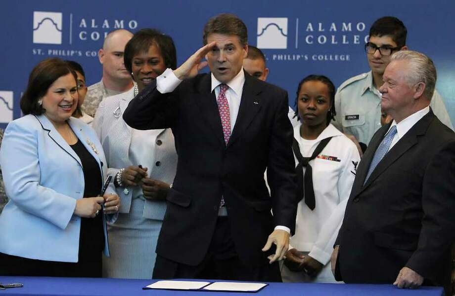Gov. Rick Perry, joined by members of the military, signs a bill to help military veterans gain college credit for their service at St. Philip's College on July 14. Photo: Kin Man Hui/kmhui@express-news.net